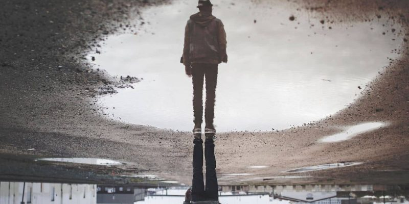 A man standing near a puddle with his reflection