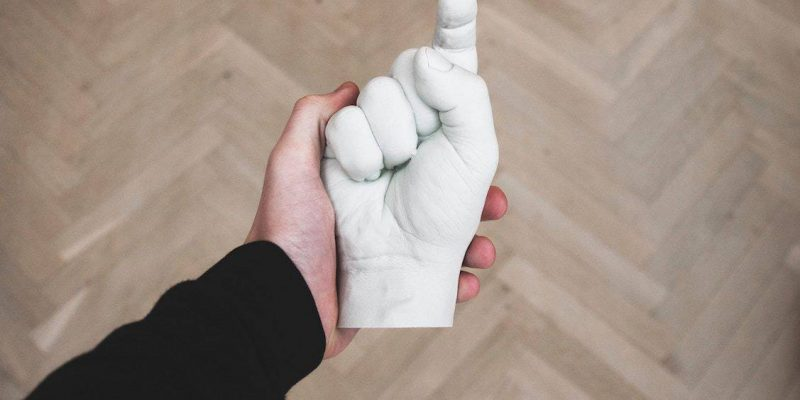 A hand holding a plaster cast of a hand pointing back at you